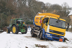 © Licensed to London News Pictures. 01/02/2019. Lower Slaughter, Gloucestershire, UK. A tractor driver helps the driver of a fuel tanker that has come stuck in the snow in Upper Slaughter after a snow shower in the Cotswolds, Gloucestershire, UK. Photo credit: LNP