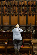 A lady visitor admires intricate wooden carvings in the choir of St. Laurences Church, Ludlow, on 11th September 2018, in Ludlow, Shropshire, England UK.