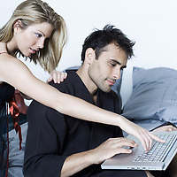 beautiful young caucasian couple in a bed on isolated background with computer laptop