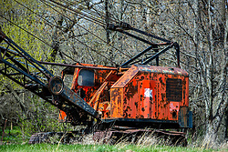 An old abandoned crane sits rusting in a pasture next to a small timber.