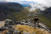 HIker Craig Weiland walks up a ridge high above Independence Mine State Historical Park and the Matanuska Valley in the Talkeetna Mountains near Hatcher Pass, Alaska.