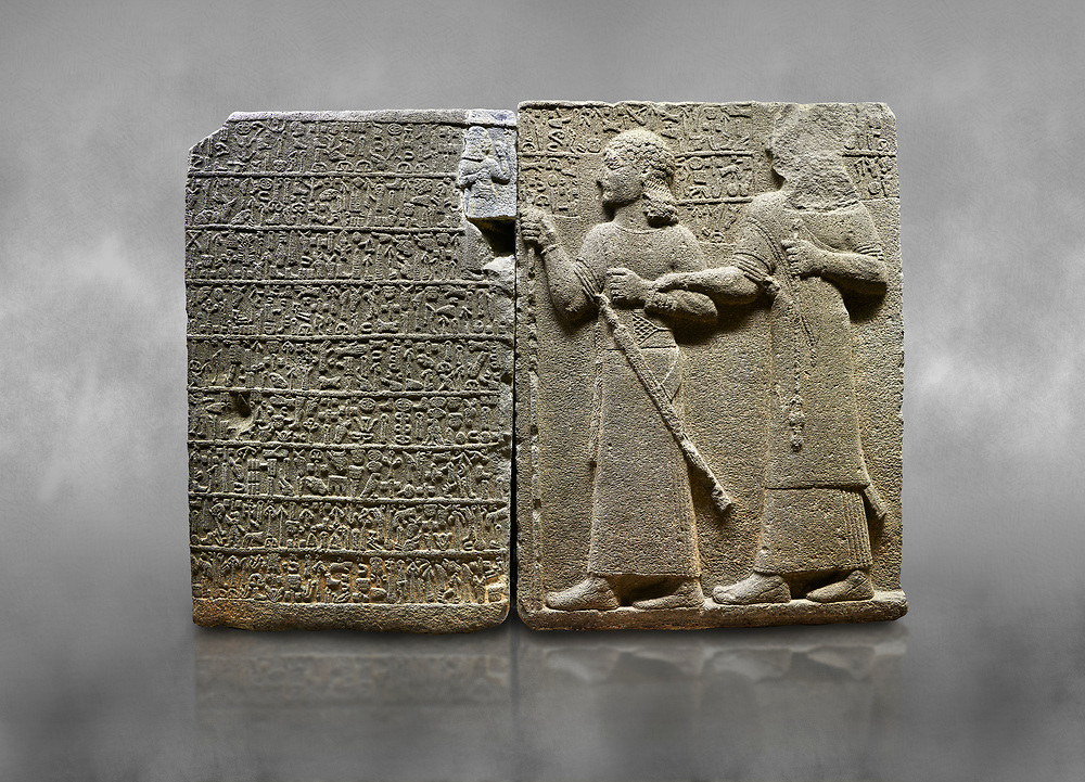 """Hittite monumental relief sculpted orthostat stone panel of Royal Buttress. Basalt, Karkamıs, (Kargamıs), Carchemish (Karkemish), 900-700 B.C. Anatolian Civilisations Museum, Ankara, Turkey.<br /> <br /> Hieroglyph panel (left) - Discourse of Yariris. Yariris presents his predecessor, the eldest son Kamanis, to his people. <br /> Right Panel - King Araras holds his son Kamanis from the wrist. King carries a sceptre in his hand and a sword at his waist while the prince leans on a stick and carries a sword on his shoulder. <br /> <br /> Hieroglyphs reads; """"This is Kamanis and his siblings. held his hand and despite the fact that he is a child, I located him on the temple. This is Yariris' image"""".  <br /> <br /> Against a grey art background. .<br />  <br /> If you prefer to buy from our ALAMY STOCK LIBRARY page at https://www.alamy.com/portfolio/paul-williams-funkystock/hittite-art-antiquities.html  - Type  Karkamıs in LOWER SEARCH WITHIN GALLERY box. Refine search by adding background colour, place, museum etc.<br /> <br /> Visit our HITTITE PHOTO COLLECTIONS for more photos to download or buy as wall art prints https://funkystock.photoshelter.com/gallery-collection/The-Hittites-Art-Artefacts-Antiquities-Historic-Sites-Pictures-Images-of/C0000NUBSMhSc3Oo"""
