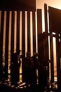 Gruppo di migranti osserva il movimento della polizia dietro la frontiera.