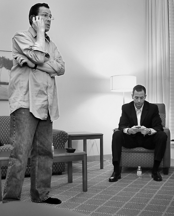 Democratic candidate for governor Dan Malloy, left, looks at his mobile device while talking on the phone in his hotel room with campaign senior advisor Roy Occhiogrosso as results come in Hartford, Conn., Tuesday, Nov. 2, 2010. (AP Photo/Jessica Hill)