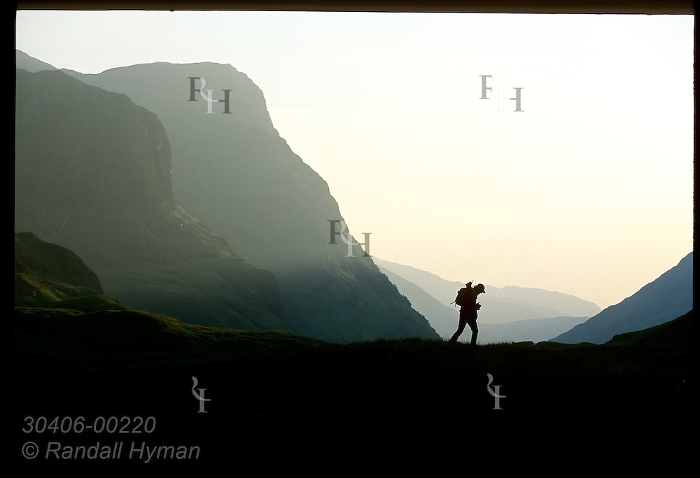 Silhouetted hiker crosses saddle of upper Glen Coe on a July eve; Glencoe, Scotland.