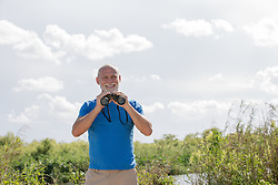 good looking mature man outdoors in The Everglades with binoculars