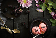 bowl of strawberry icecream on black wood with flowers