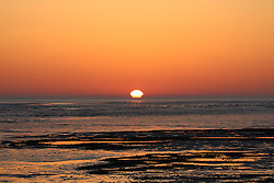 © Licensed to London News Pictures. 15/04/2015.  Sunrise at the Thames estuary on what is predicted to be the hottest day of the year so far. The sun rises above the river as seen from Allhallows in Kent as this week's fine weather continues. Credit : Rob Powell/LNP