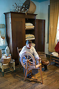 Craftsperson spinning cotton, Vermilionville museum of Acadian Cajun, Creole, Native American culture, Lafayette, Louisiana, USA