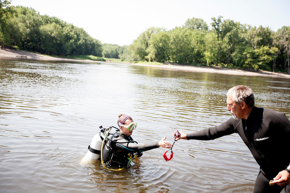 Byron Karns, right, hands an underwater camera to fellow National Park Service biologist Allie Holdhusen during a dive to collect mussels for observation in the Mississippi River near Pike Island August 14, 2015. Endangered mussel species have been reintroduced in the area, and multiple agencies are working together to assess the health of all mussels in the river.