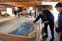 Christine Hadsel from Curtains with Borders points out damage to Warren Huse on the curtain found in the Lakeport Opera House.  (Karen Bobotas/for the Laconia Daily Sun)
