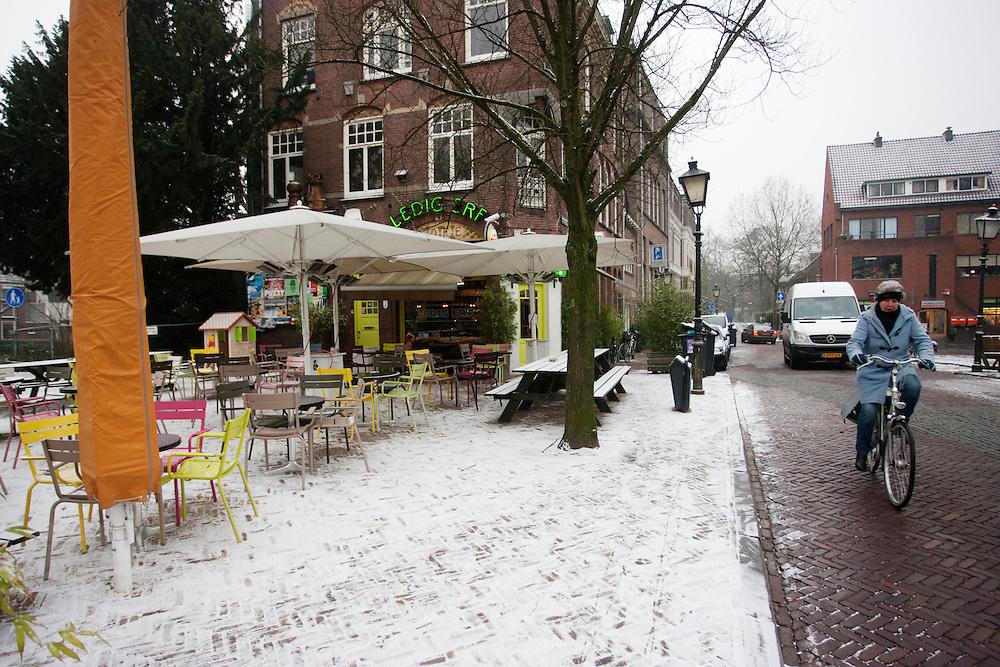 Een vrouw fietst langs een besneeuwd terras aan het Ledig Erf in Utrecht.<br /> <br /> A woman is cycling near a snowy terrace at Ledig Erf in Utrecht.