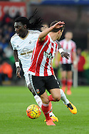 Swansea's Bafetimbi Gomis (l) takes on Southampton's Cedric Soares. Barclays Premier league match, Swansea city v Southampton at the Liberty Stadium in Swansea, South Wales on Saturday 13th February 2016.<br /> pic by  Carl Robertson, Andrew Orchard sports photography.