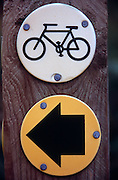 Close up of wooden fence post with two circular signs, cycle route and direction arrow, Suffolk, England, UK