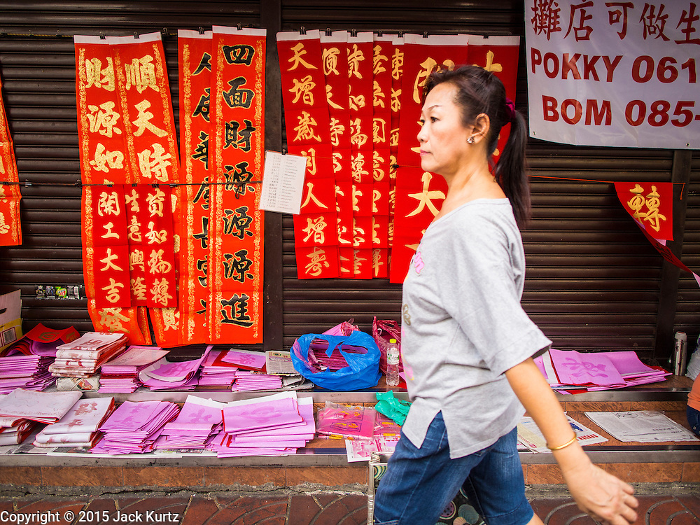 """17 FEBRUARY 2015 - BANGKOK, THAILAND:  A woman walks by Chinese New Year banners for sale in Bangkok's Chinatown. Chinese New Year is February 19 in 2015. It marks the beginning of the Year of Sheep. The Sheep is the eighth sign in Chinese astrology and the number """"8"""" is considered to be a very lucky number. It symbolizes wisdom, fortune and prosperity. Ethnic Chinese make up nearly 15% of the Thai population. Chinese New Year (also called Tet or Lunar New Year) is widely celebrated in Thailand, especially in urban areas like Bangkok, Chiang Mai and Hat Yai that have large Chinese populations.      PHOTO BY JACK KURTZ"""