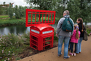 London 2012 Olympic Park in Stratford, East London. People stop to look at an artwork of a deconstructed old fashioned red telephone call box.