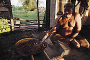 Auseuga Lagavale, the matai (head) of his extended family, roasts nuts over a low fire in the cooking hut, in preparation for a White Sunday feast at the Lagavale home in Poutasi Village, Western Samoa. The Lagavale family lives in a 720-square-foot tin-roofed open-air house with a detached cookhouse in Poutasi Village, Western Samoa. The Lagavales have pigs, chickens, a few calves, fruit trees and a vegetable garden. Material World Project.