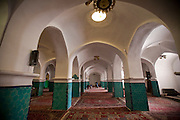 Interior of Jameh Mosque in the city of Yazd, Iran. A worker vacuums the carpets.