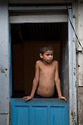 A boy looks from his home in Vila Dos Pescadores favela, Cubatão