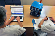 Nederland, Nijmegen, 14-1-2013Twee verpleegkundigen werken aan een tafel aan dossiers van de patienten op hun afdeling. De een doet dat met een computer, de ander in een geschreven status. Electronisch patienten dossier, patientendossier.Foto: Flip Franssen