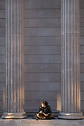 A young man sits cross-legged to read his book beneath the tall columns of the Bank of England on Threadneedle Street in the heart of the City of London, the capitals financial district, on 27th February 2021, in London, England.