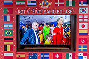 The Portuguese and Spanish football teams are shown on a street TV screen bordered by international flags before their game in the 2018 World Cup in Russia, in the Slovenian capital, Ljubljana, on 25th June 2018, in Ljubljana, Slovenia. Above the screen it reads: Just like in the living room just better.