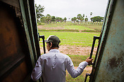 01 JULY 2006 - PHNOM PENH, CAMBODIA: A passenger leans out the door of the Phnom Penh - Battambang train as it travels through rural Cambodia. While much of Cambodia's infrastructure has been rebuilt since the wars which tore the country apart in the late 1980s, the train system is still in disrepair. There is now only one passenger train in the country. It runs from Phnom Penh to the provincial capitol Battambang and it runs only one day a week. It takes 12 hours to complete the 190 mile journey.  Photo by Jack Kurtz / ZUMA Press