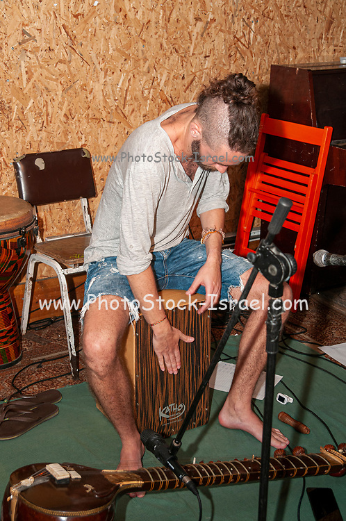 Young man plays the Cajon a box-shaped percussion instrument originally from Peru