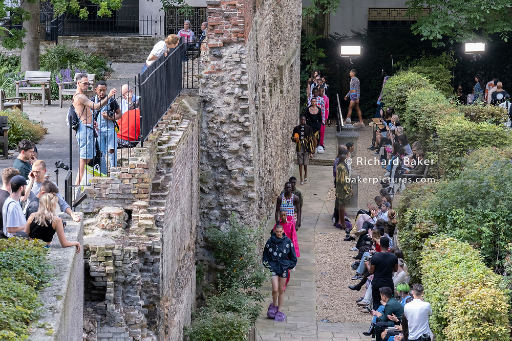 Beneath the remains of London's Roman wall perimeter, models parade clothing styles during London fashio Week, on 21st September 2021, in the City of  London, England.