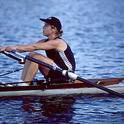 A woman rowing a racing scull on the Charles River between Boston and Cambridge, MA