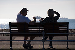 © Licensed to London News Pictures. 27/10/2017. Portsmouth, UK.  A man and woman sat on a bench looking out to watch HMS Westminster in the sunny autumn weather on Southsea promenade today, 27th October 2017.  Photo credit: Rob Arnold/LNP