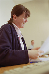 Woman sitting at desk in translation agency office; laughing,