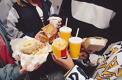 Children holding selection of fast food including fizzy drinks; burger; chips and pie,