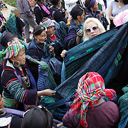 Black Hmong and Red Dzao women hard sell their goods to western tourists in Sapa market place, Northern Vietnam. Sapa and the surrounding highlands are close to the Chinese border in Northern Vietnam and is inhabited by highland minorities including Hmong and Dzao groups. Sapa is now a thriving tourist destination for travelers taking the night train from Hanoi. Sapa, Vietnam. 16th March 2012. Photo Tim Clayton