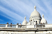 Tourists enjoy the views of the city  from the Sacre Coeur Basilica at the top of Montmartre, Paris, France.