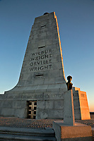 NC01437-00...NORTH CAROLINA - Sunrise light on the monument to the Wright brothers at the site of their first flight at Kitty Hawk on the sand dunes of the Outer Banks.