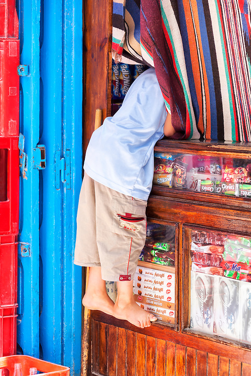 Little boy looking behind the curtain at a little shop.
