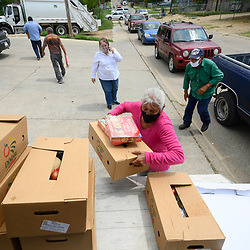 Local volunteers including Gloria Romo distribute dozens of food boxes to the colonia of El Cenizo about 10 miles south of Laredo along the Texas-Mexico border. About 450 families are served twice a week with staples and fresh fruit in an effort sponsored by Latin American Lutheran Mission (LALM).