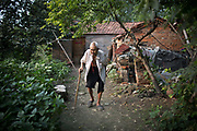 87 year old Dou Shengli walks out of his home at a rural village near Fuyang, Anhui Province,  China on 28 August  2013.  As able-bodied adults seek work in cities in hopes of better income, more and more villages in China are inhabited mostly by the elderly and children.