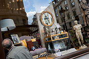 Watched by a statue of the ancient Greek God Apollo, a window shopper looks into the Osprey retailer in Lower Regent Street, on 2nd May 2019, in London, England.