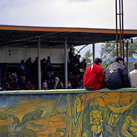 Americas, South America, Chile, Puerto Natales. Fans sit on the wall to watch the local futbol (soccer) team play on a Sunday afternoon in Puerto Natales.