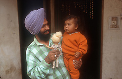 Man standing in doorway holding baby and doll; Punjab; India,