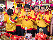 """23 JUNE 2015 - MAHACHAI, SAMUT SAKHON, THAILAND: Community leaders in Mahachai pray before taking the City Pillar Shrine out for the procession through town. The Chaopho Lak Mueang Procession (City Pillar Shrine Procession) is a religious festival that takes place in June in front of city hall in Mahachai. The """"Chaopho Lak Mueang"""" is  placed on a fishing boat and taken across the Tha Chin River from Talat Maha Chai to Tha Chalom in the area of Wat Suwannaram and then paraded through the community before returning to the temple in Mahachai.   PHOTO BY JACK KURTZ"""