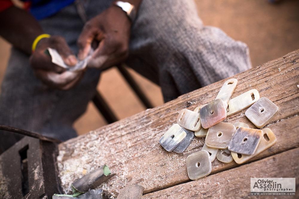 A man sands small pieces of cow horn at the Village Artisanal de Ouagadougou, a cooperative that employs dozens of artisans who work in different mediums, in Ouagadougou, Burkina Faso, on Monday November 3, 2008.