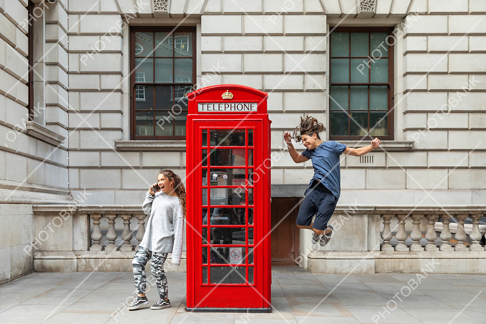 Girl is leaning against the phone booth with a smartphone and from the other side a boy leaps with joy.