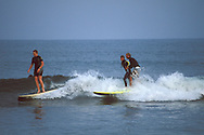 Tandem Surfers riding surfboard on waves at Surfrider Beach State Park, Malibu, Los Angeles County, California