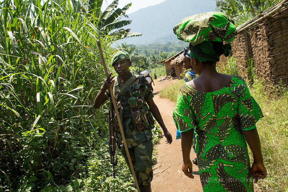 CLIENT: AL JAZEERA AMERICA<br /> <br /> Kikandi Batende, who is nine moths pregnant, and Mariam Rizik, right, five months pregnant, both 26 years old, walk past a government soldier in their village of Lukweti, Masisi in conflict-ridden North Kivu, Democratic Republic of Congo. The village sits at the crossroads of several local rebel groups and has not been treated much better at the hands of the poorly paid government soldiers, the FARDC, who also reportedly raped, looted and attacked villagers.