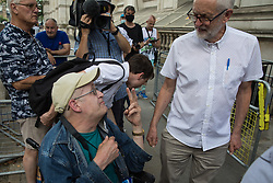 London, UK. 20th July, 2021. Former Labour Party leader Jeremy Corbyn chats to a disability activist in Whitehall after accompanying NHSPay15 campaigners to deliver a petition signed by over 800,000 people calling for a 15% pay rise for NHS workers to 10 Downing Street.