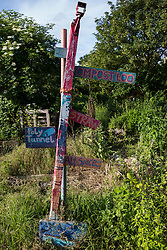 Sipson, UK. 5th June, 2018. A signpost is pictured at Grow Heathrow. Grow Heathrow is a squatted off-grid eco-community garden founded in 2010 on a previously derelict site close to Heathrow airport to rally support against government plans for a third runway and it has since made a significant educational and spiritual contribution to life in the Heathrow villages, which remain threatened by Heathrow airport expansion.