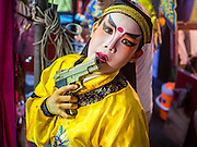 "14 MAY 2015 - BANGKOK, THAILAND: A child who performs in the Chinese opera with his toy gun backstage at the Pek Leng Keng Mangkorn Khiew Shrine in the Khlong Toey slum in Bangkok. Chinese opera was once very popular in Thailand, where it is called ""Ngiew."" It is usually performed in the Teochew language. Millions of Chinese emigrated to Thailand (then Siam) in the 18th and 19th centuries and brought their culture with them. Recently the popularity of ngiew has faded as people turn to performances of opera on DVD or movies. There are still as many 30 Chinese opera troupes left in Bangkok and its environs. They are especially busy during Chinese New Year and Chinese holiday when they travel from Chinese temple to Chinese temple performing on stages they put up in streets near the temple, sometimes sleeping on hammocks they sling under their stage. Most of the Chinese operas from Bangkok travel to Malaysia for Ghost Month, leaving just a few to perform in Bangkok.       PHOTO BY JACK KURTZ"
